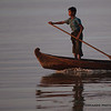 A boy stands on the bow of his boat to help guide it through the river.